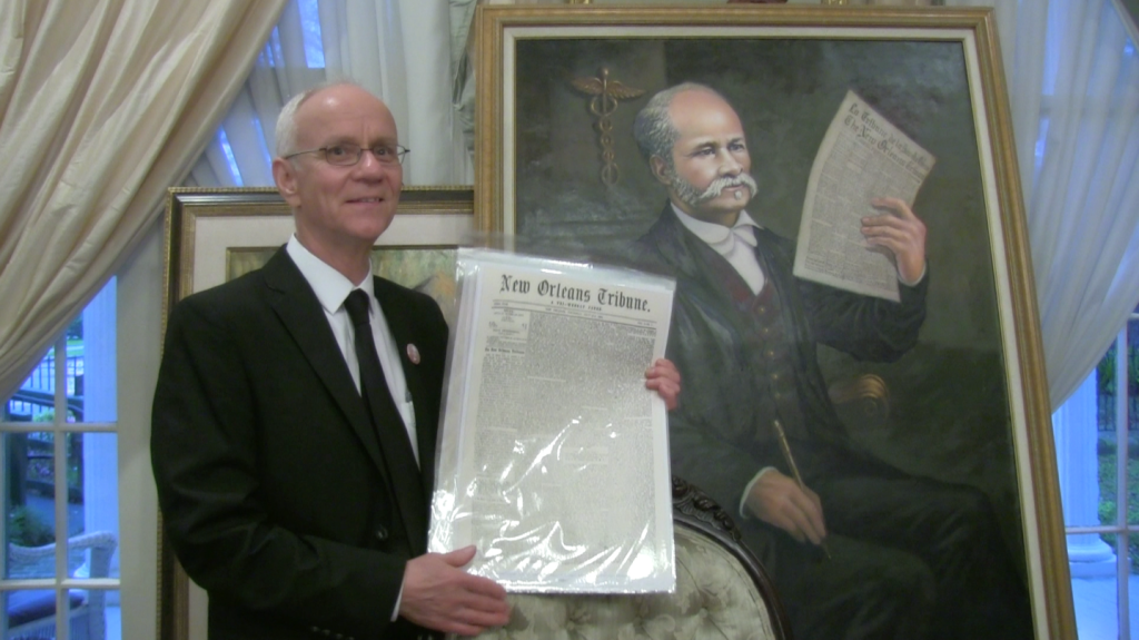 Mark Charles Roudané with portrait of Dr. Louis Charles Roudanez, at Le Musée de f.p.c. Artwork by Ulrick Jean-Pierre.